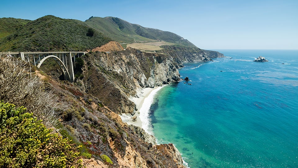 Bixby Bridge on a perfect summer day, Pacific Coast Highway Route 1, California. Beautiful bay full of clear blue water and famous landmark Bixby Bridge.